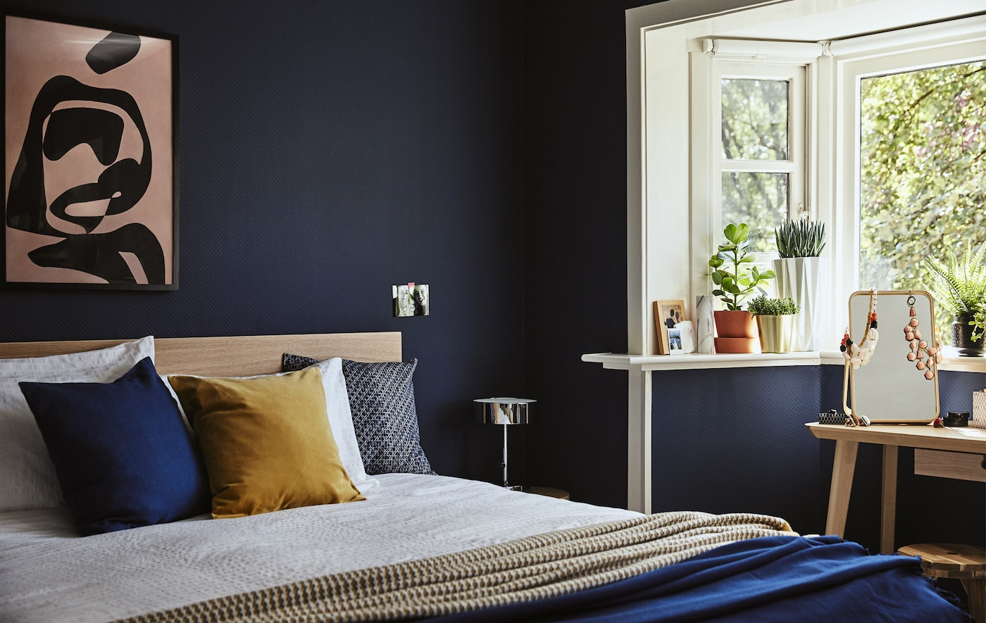 A corner of a dark blue bedroom with a double bed and plant pots on the windowsill.