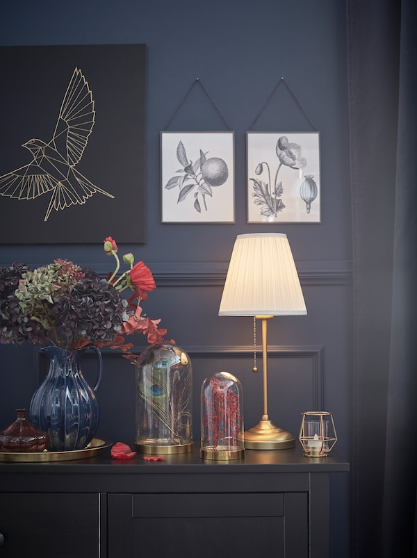 A corner of a dark-panelled room with art and decorations on both walls and surfaces, all softly lit by an ÅRSTID lamp.
