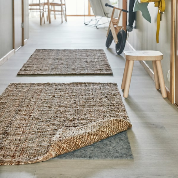 A corner of a jute rug is lifted and under it lies a STOPP FILT rug underlay with anti-slip which keeps the rug in place.