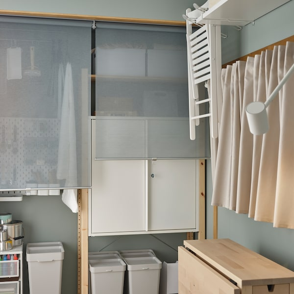 A corner of a room with cupboards and storage boxes in a pine frame shelving unit. A table is folded up beside the wall.