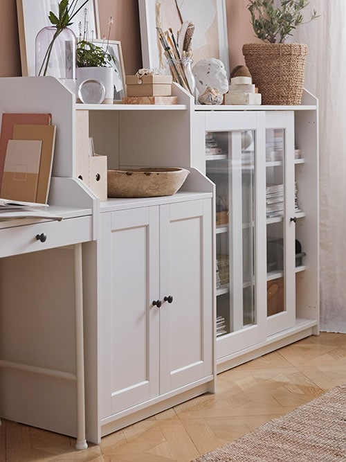 A corner of a room with white storage and display cabinets, decorated with items  in natural textures.