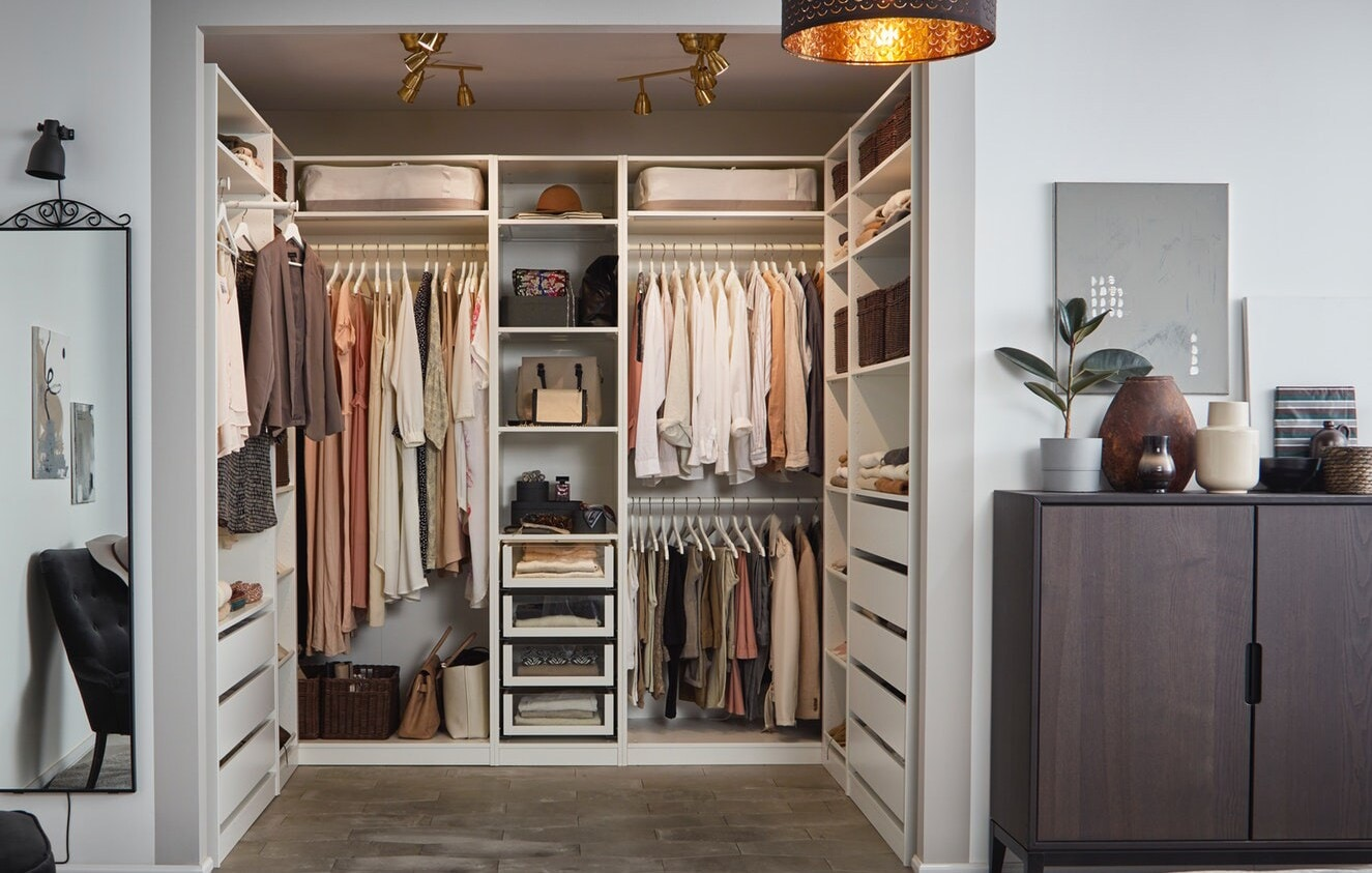 A corner PAX Wardrobe System in white neatly organized with clothes and storage boxes in a bedroom.