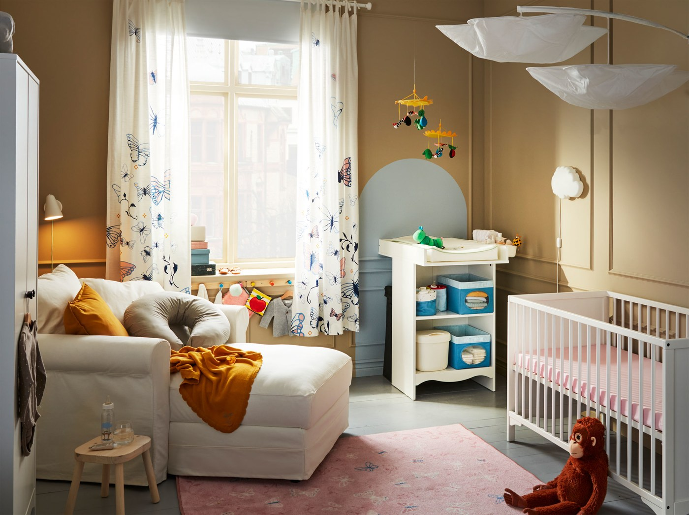 A cosy baby room, with a white IKEA GRÖNLID chaise longue, an IKEA SOLGUL changing table, a white cot, soft toys and mobiles.