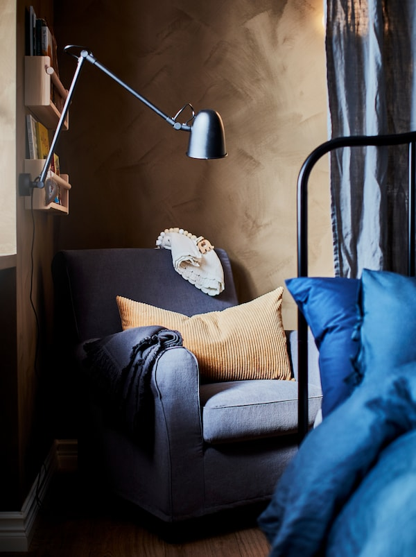 A cosy bedroom corner with a blue GRÖNLID armchair, a light brown pillow, children's books on the wall and a reading lamp.