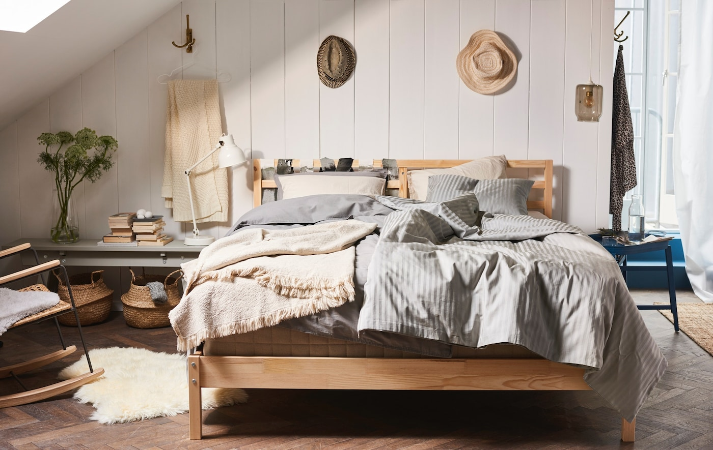 A cosy bedroom in earthy tones and materials. A wooden bed has many layers of textiles on top. In the back the white wooden panneling is visible.