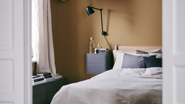 A cosy bedroom with rich caramel walls and the MALM bed frame, a wall lamp and a bedside table.
