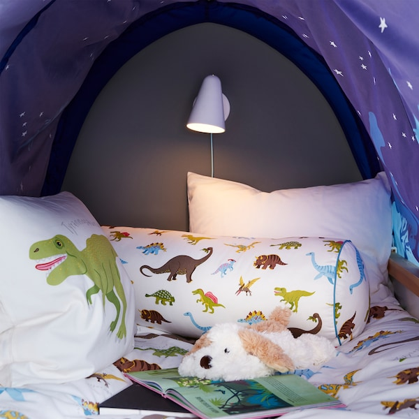 A cosy nook with a blue bed tent, a dog soft toy, a white wall lamp, an open book and cushions with dinosaur patterns.