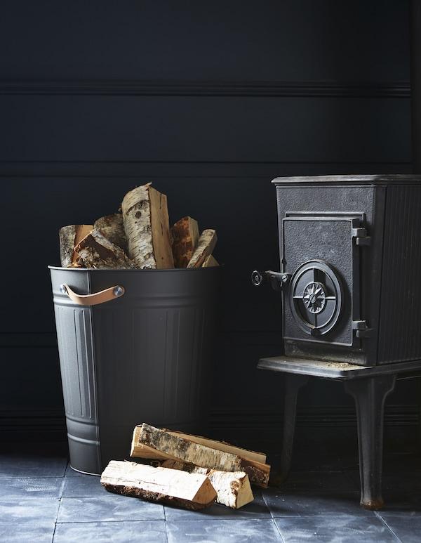 À côté d'une cheminée, poubelle KNODD avec poignées en cuir utilisée comme rangement pour le bois.