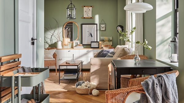 A country chic space with light green walls, a mix of white, pine wood, and wicker furniture, and quirky décor.