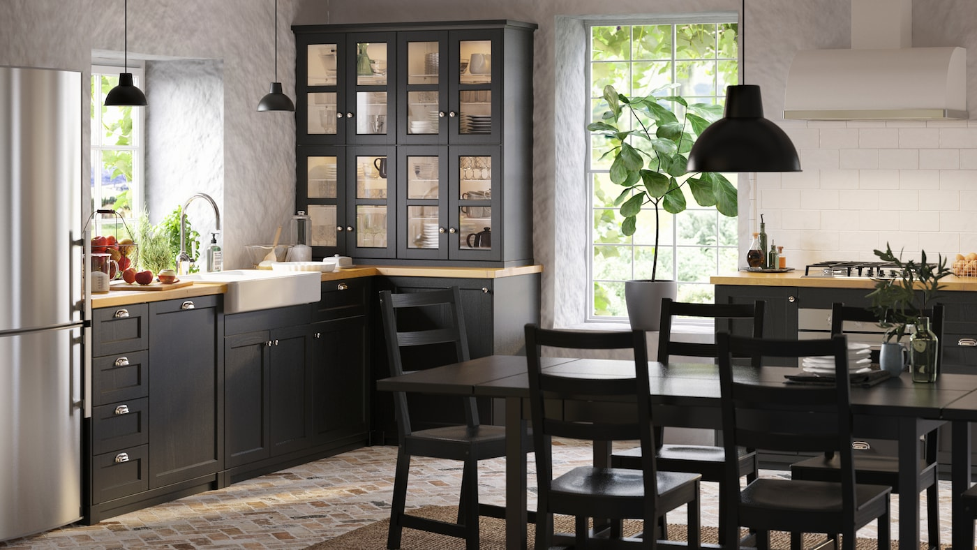 A country-style kitchen with black stained LERHYTTAN kitchen fronts, a black NORDVIKEN extendable table and NORDVIKEN chairs.