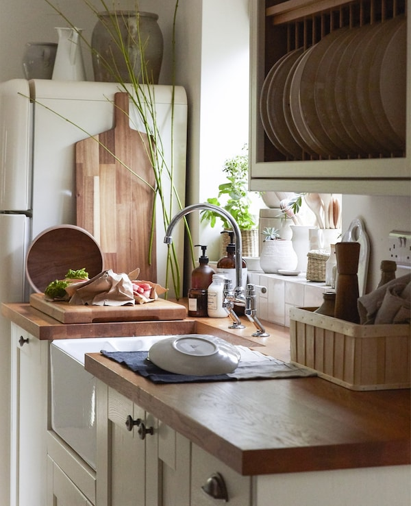 A country-style kitchen with wooden countertops, cream cupboards and open storage.