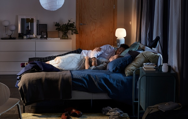 A couple cuddle asleep in a SLATTUM upholstered bed, with a SYMFONISK lamp/speaker lit in the background.