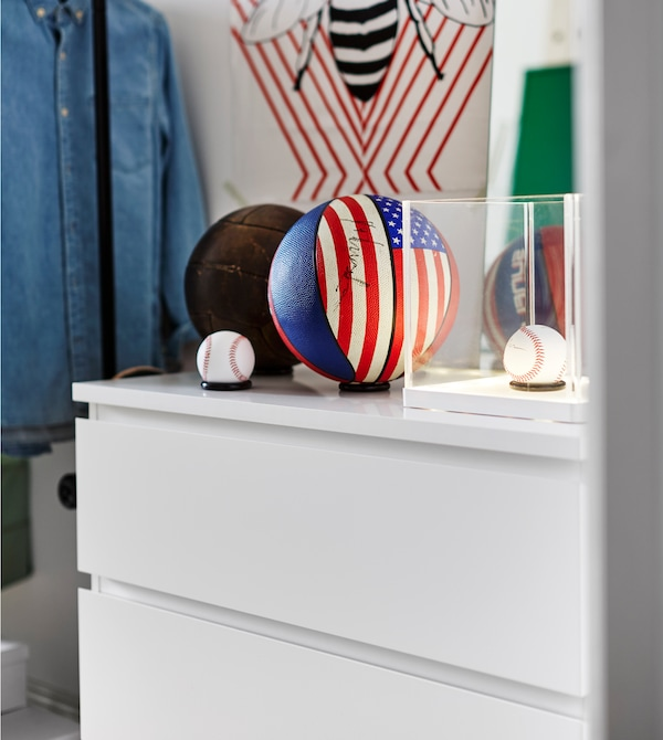 A couple of baseballs and basketballs sit on top of a white chest of drawers.