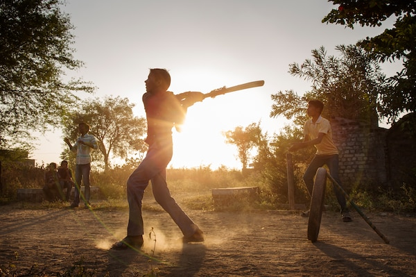 A couple of boys are playing cricket outside in the dirt. The sun is setting behind them.