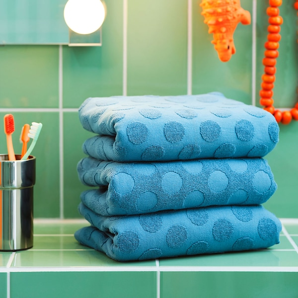 A couple of folded blue MÅLSELVA towels and a KALKGRUND toothbrush holder placed on green tiles.