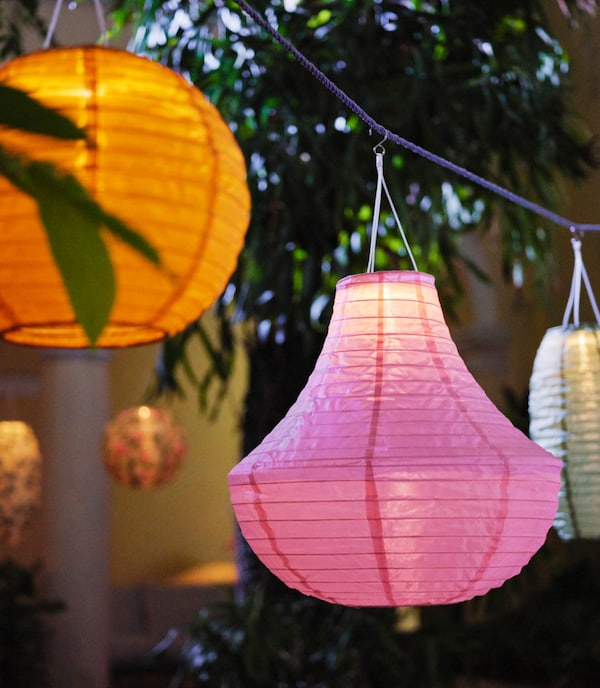 A couple of lanterns in orange, pink and white hanging from a blue rope with greenery in the background.