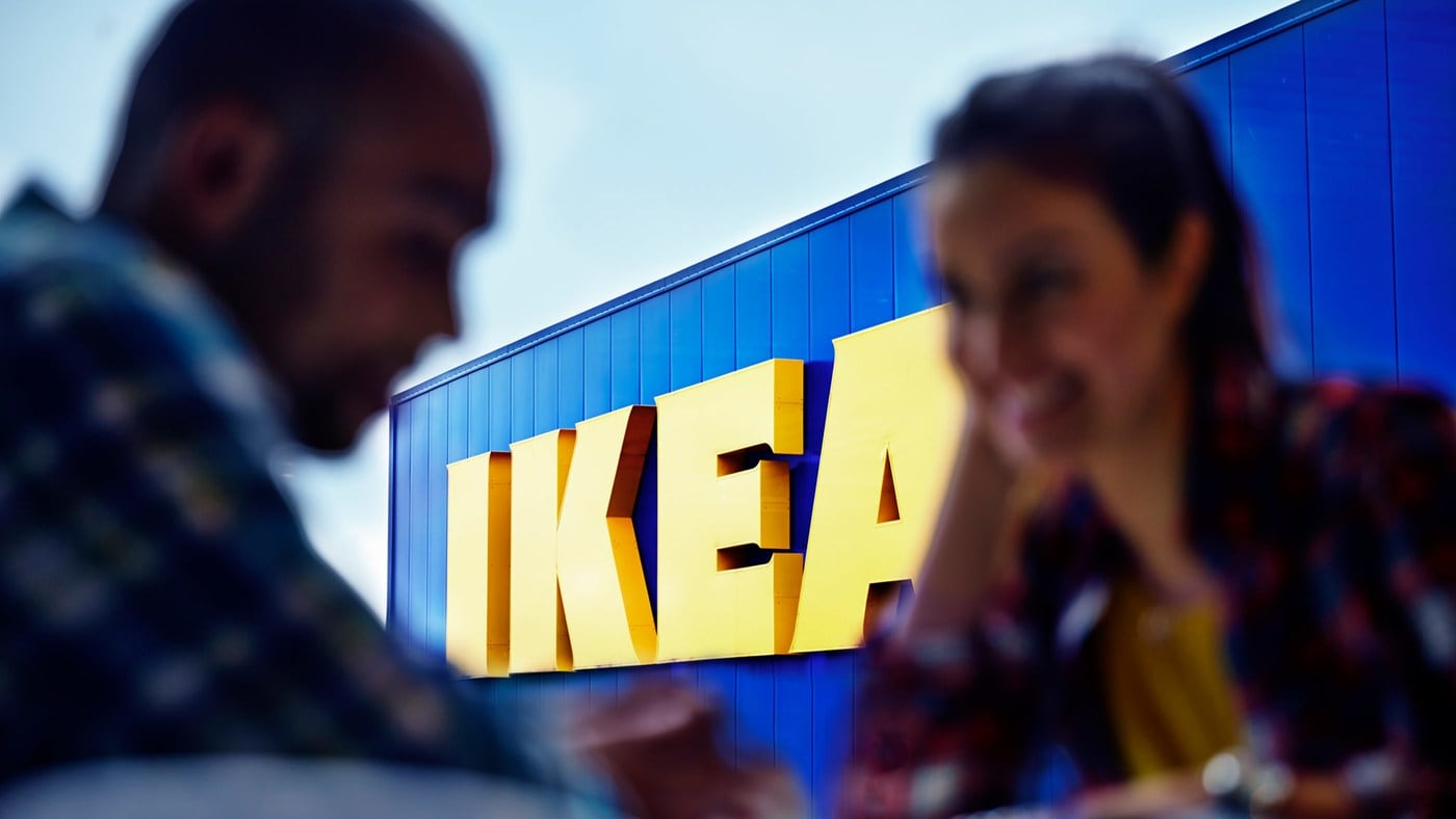 A couple outside of the IKEA storefront, with the bright yellow IKEA store logo in focus.