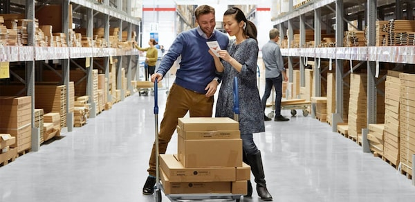 A couple shopping in an IKEA warehouse pushing a flat cart with boxes on top