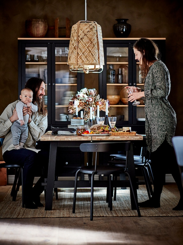 A couple with a baby gathered around a dining table. Dark glass-door cabinets with table accessories by the far wall.