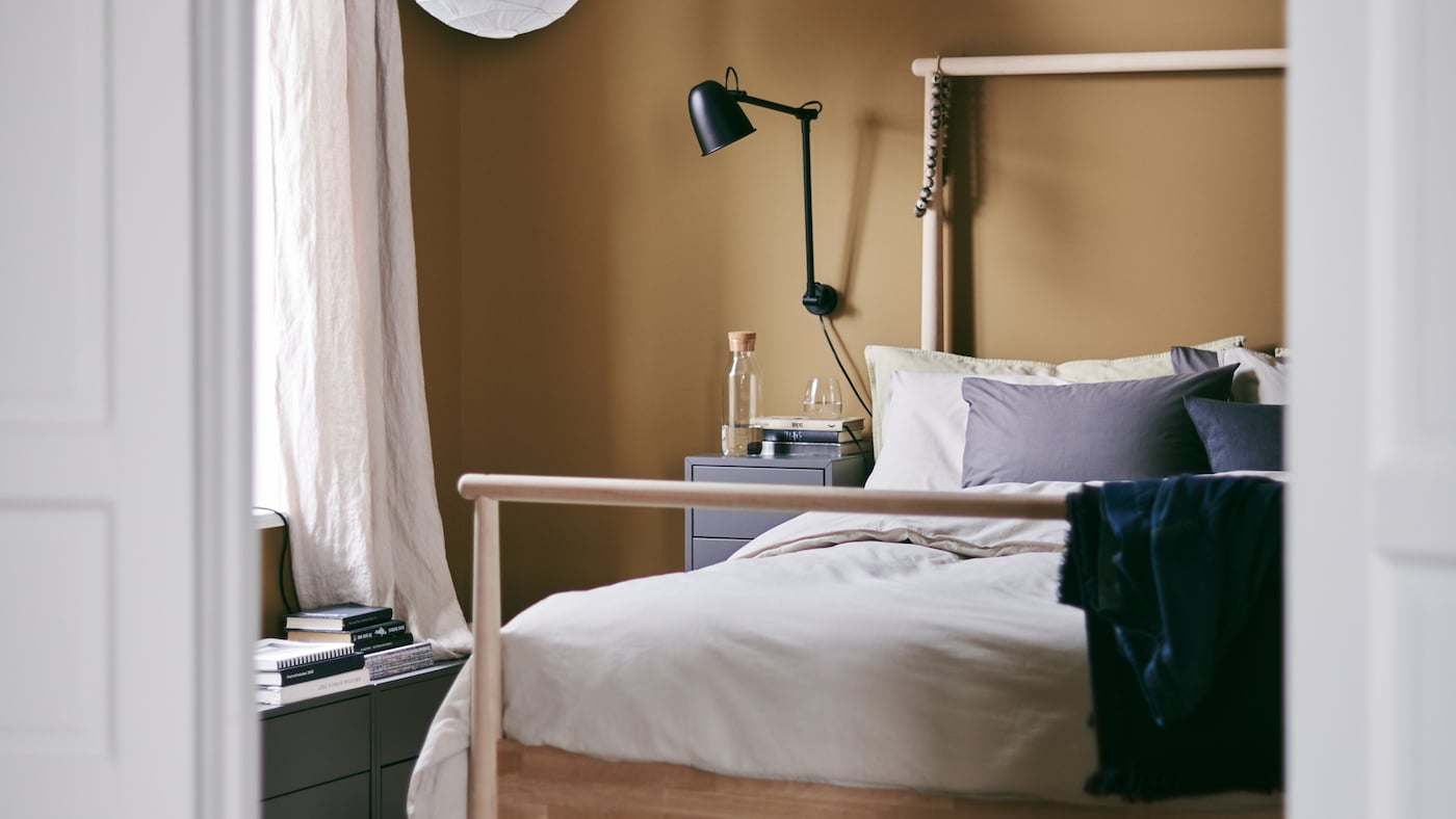 A cozy bedroom with rich caramel walls and the GJÖRA bed frame made of solid birch and a bedside table.