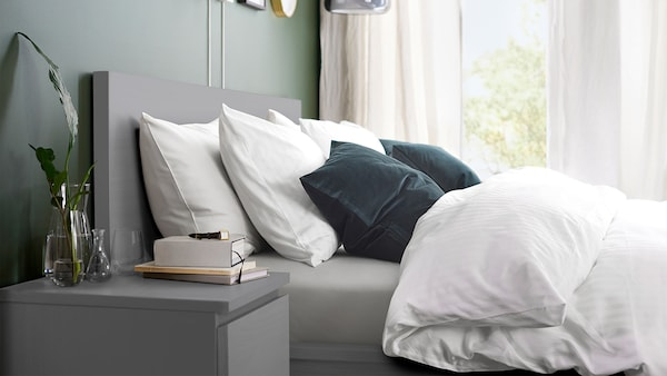 A cozy grey MALM bed with fluffy white linens.