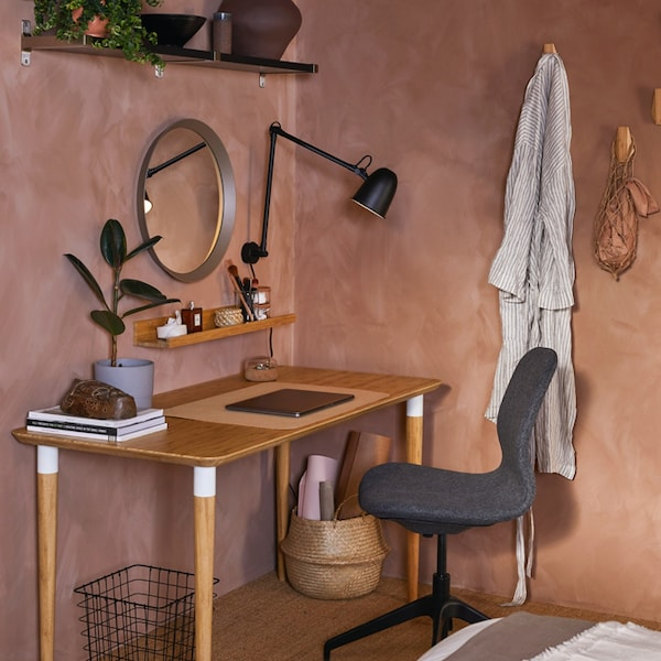 A cozy home office space with a HILVER desk in birch and a desk chair covered in a blanket.