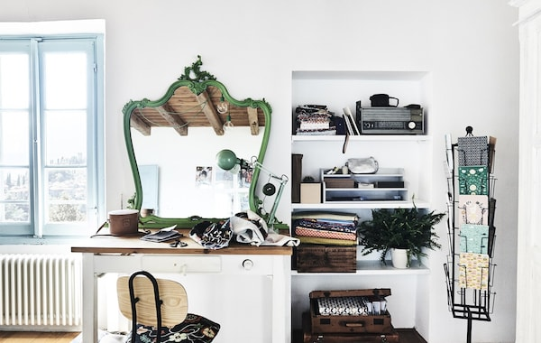 A craft space with desk, white walls and green mirror.