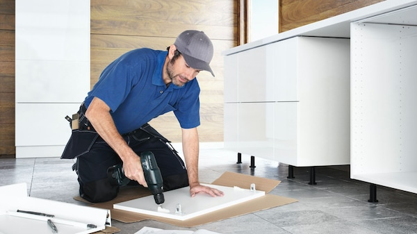 A craftsman assembles a kitchen cupboard with a cordless screwdriver