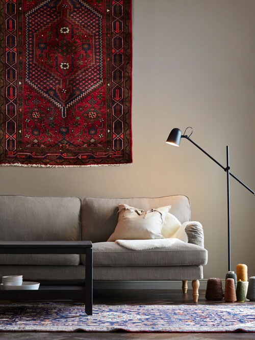 A cream sofa with ornate rugs on the floor and wall.