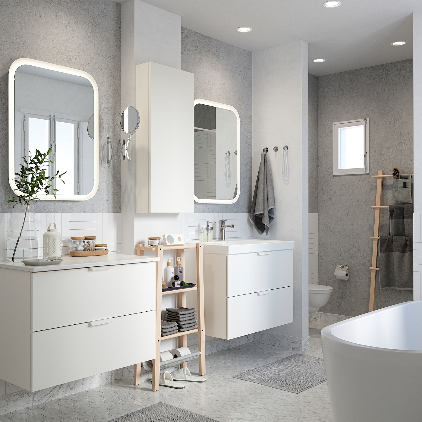 A crisp white bathroom with two wash stands, two mirrors with integrated lighting and bath mats and towels in grey.