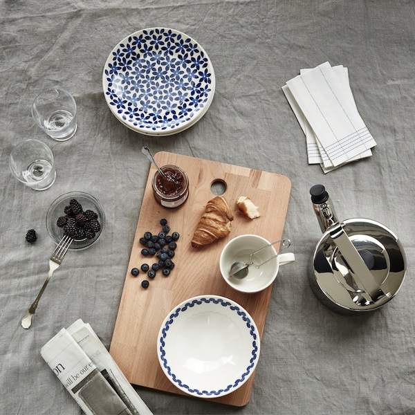 A croissant, jam and berries on a wooden board with patterned plates and bowls, a teapot and a newspaper.