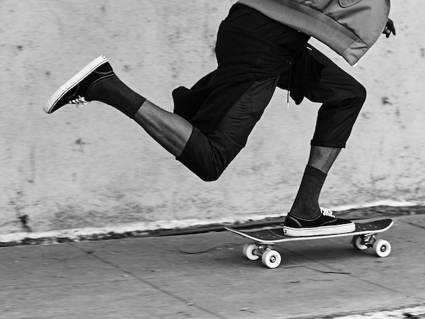 A cropped black and white image showing a young man's legs skateboarding up a sidewalk.