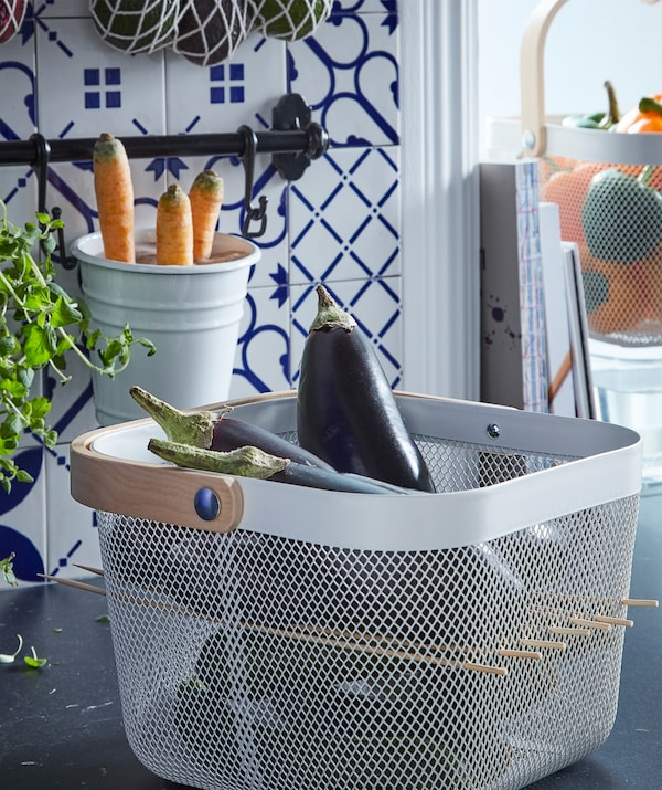 A cube-shaped RISATORP basket filled with aubergines. Wooden skewers have been inserted in the mesh to create a shelf.