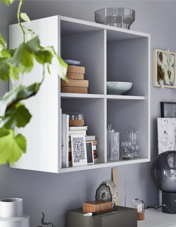A cubed wall storage unit with decorative objects inside.