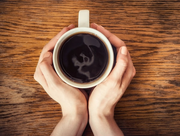 A cup of coffee between two hands.