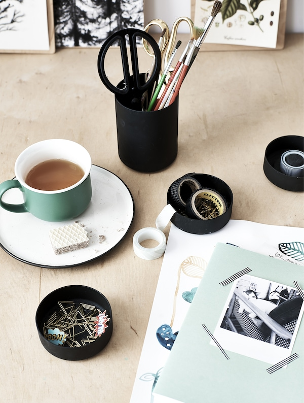 A cup of tea and stationery on a wooden desk.