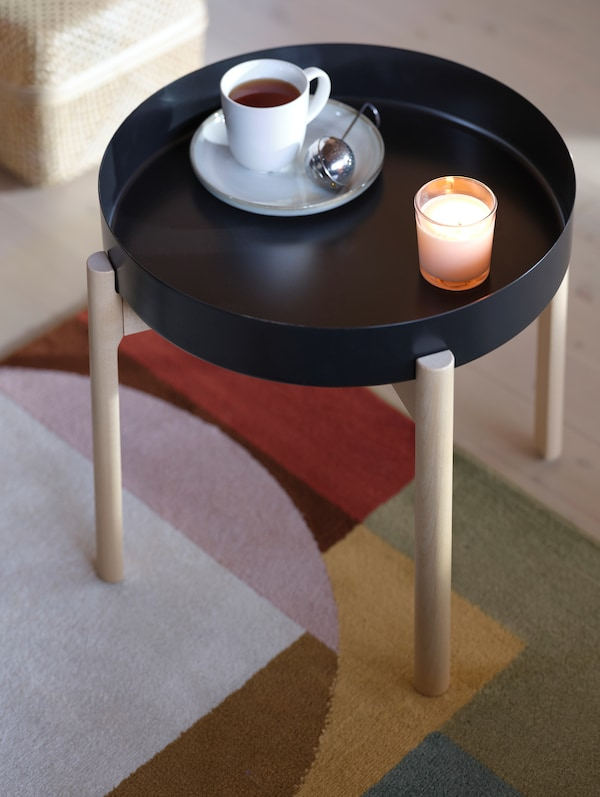 A cup of tea and strainer sit on an YPPERLIG side table, alongside a lit candle that creates a cosy atmosphere.