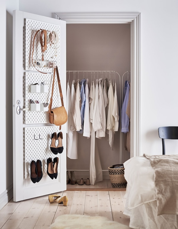 A cupboard with clothes rack and open door with peg board holding accessories.