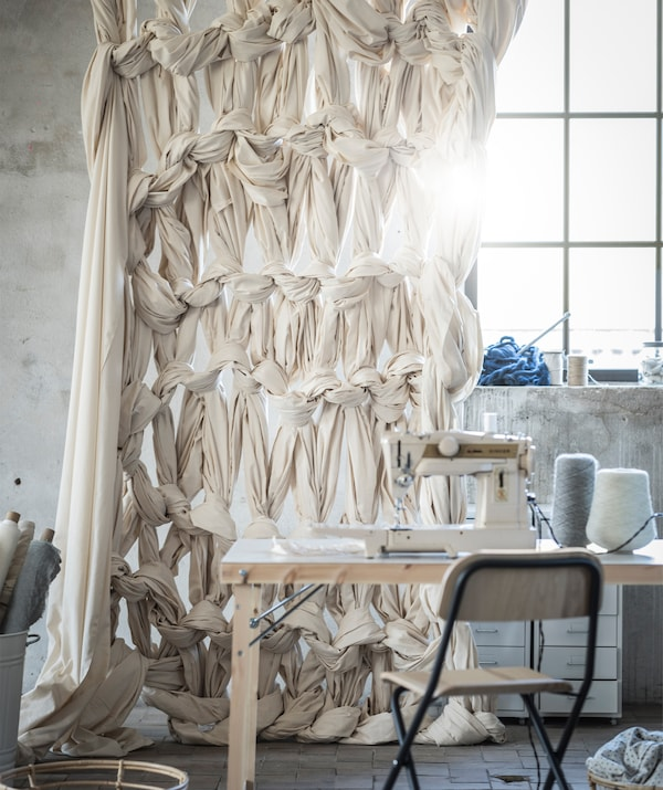 A curtain made of knotted fabric hangs behind a table with a sewing machine on top.