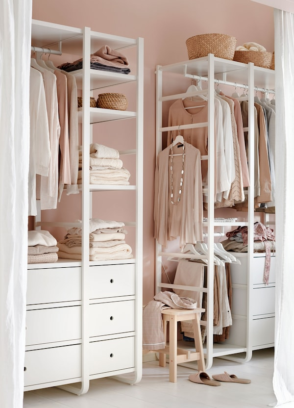 A curtained nook containing an IKEA ELVARLI open storage system filled with clothing.