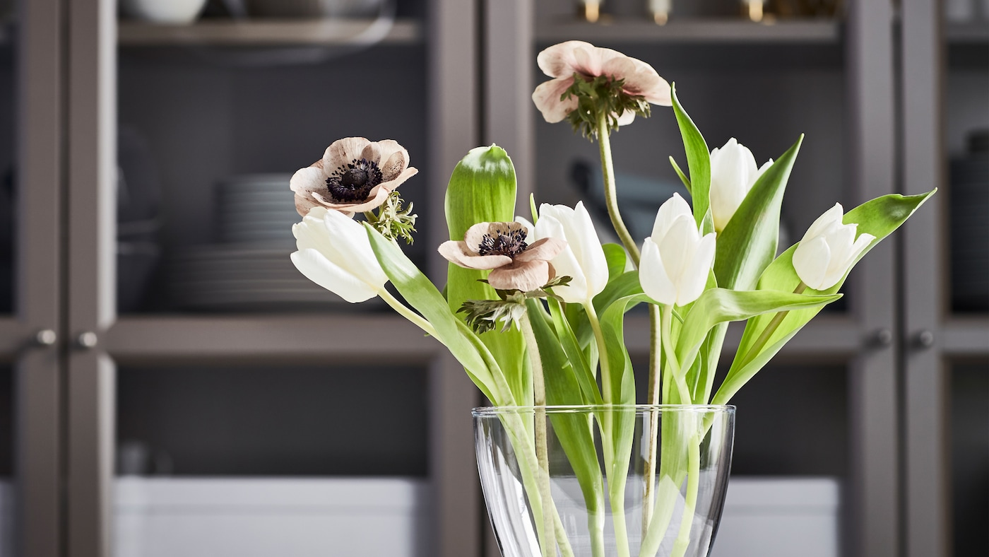 A curvy VASEN vase with a small bouquet of white tulips, brownish poppies and fresh green leaves in front of a cupboard.
