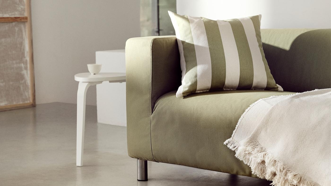 A cushion in a green natural/striped HILDAMARIA cushion cover sits on a yellow-green KLIPPAN sofa along with a throw.