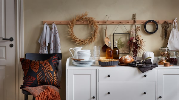 A cushion, throw, pie dish, cloth napkins and other items from the HÖSTKVÄLL collection decorate a HAUGA sideboard.