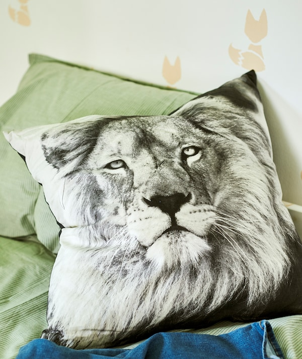 A cushion with a black and white photo of a lion on a bed with green bedding, the wall is stencilled with a fox pattern.
