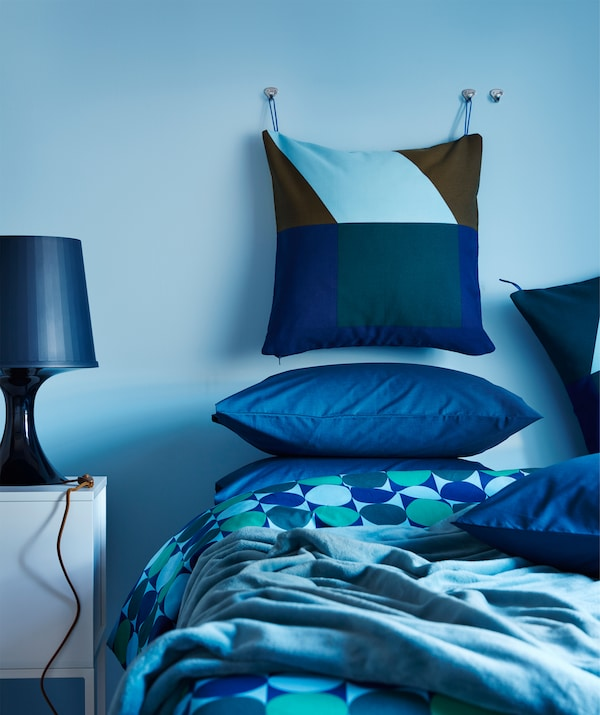 A cushion with a blue and green IKEA MAJALISA cushion acover hanging on a bedroom wall, in a bedroom with blue textiles.