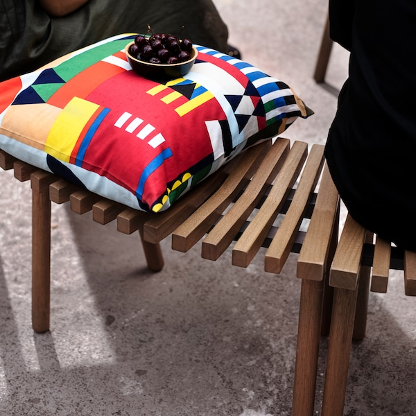 A cushion with a multicoloured graphic pattern on a curved wooden bench, both from the ÖVERALLT collection.