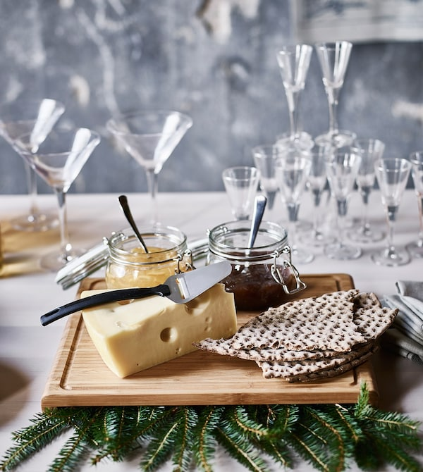 A cutting board with a block of cheese, crisp bread and jars of jam.