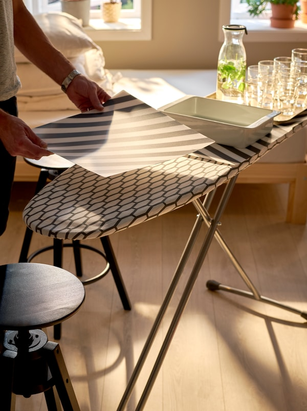 A DÄNKA ironing board being set with serving trays and stacks of glasses and PIPIG place mats protecting the textile surface.