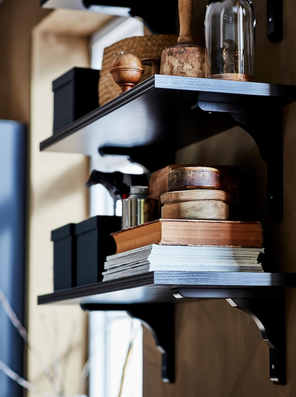 A dark BERGSHULT/RAMSHULT wall shelf laden with a stack of magazines and books, boxes and display storage.