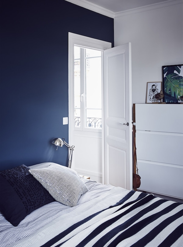 A dark blue and white bedroom.